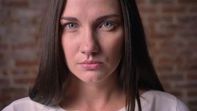 Ritratto del primo piano di una donna, che guarda seriamente nella macchina fotografica sull'per bricken il fondo archivi video