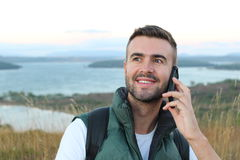 Ritratto del primo piano, giovane uomo estatico felice con la mano sugli occhi spalancati e bocca parlanti sul telefono cellulare fotografie stock