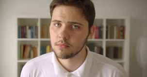 Ritratto del primo piano del maschio caucasico bello che esamina macchina fotografica nella biblioteca