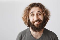 Ritratto del primo piano del maschio orientale maldestro con capelli ricci e della barba che sorridono con il dubbio e l'esitazio fotografia stock