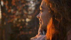 Ritratto del primo piano nel profilo della ragazza caucasica riccio-dai capelli che guarda lateralmente allegro nel parco autunna fotografia stock
