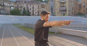 Ritratto del primo piano del pareggiatore maschio sportivo caucasico adulto che allunga armi sullo stadio nella città urbana all' archivi video