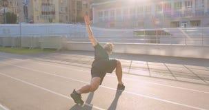 Ritratto del primo piano del pareggiatore maschio sportivo caucasico adulto che allunga sullo stadio nella città urbana all'apert stock footage