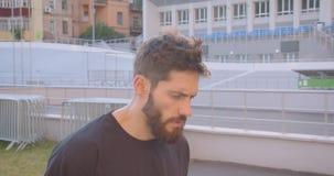 Ritratto del primo piano del pareggiatore maschio sportivo caucasico adulto che cammina sullo stadio nella città urbana all'apert archivi video