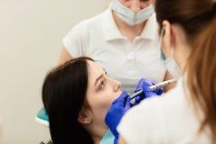 Ritratto del primo piano del paziente della giovane donna, sedentesi nella sedia del dentista Medico esamina i denti Prevenzione  fotografia stock
