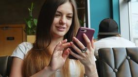 Ritratto del primo piano del telefono cellulare di uso della giovane donna in caffè video d archivio