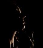 Ritratto del profilo pensieroso della ragazza di bella sensualità con gli occhi chiusi in uno scuro, su un fondo nero Fotografie Stock