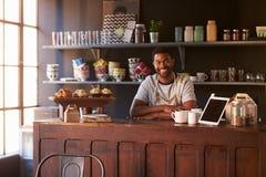Ritratto del proprietario di caffetteria maschio che sta dietro il contatore immagini stock libere da diritti
