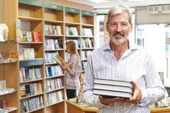 Ritratto del proprietario maschio della libreria con il cliente nel fondo Immagine Stock