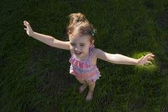 Ritratto del punto di vista superiore della bambina su fondo di erba verde Fotografie Stock Libere da Diritti