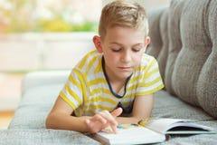 Ritratto del ragazzino abile con il libro di lettura Immagine Stock