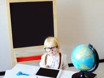 Ritratto del ragazzino che esamina macchina fotografica nel luogo di lavoro Fotografie Stock Libere da Diritti