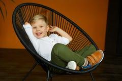 Ritratto del ragazzino che si siede nella sedia sopra fondo giallo Immagini Stock Libere da Diritti
