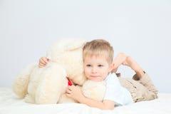 Ritratto del ragazzino con l'orsacchiotto a casa fotografie stock