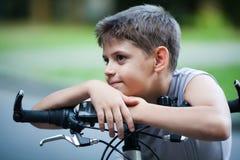 Ritratto del ragazzino su una bicicletta all'aperto Fotografia Stock