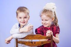 Ritratto del ragazzino sveglio e della ragazza che si siedono sulla sedia Immagine Stock