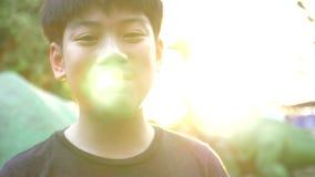 Ritratto del ragazzo asiatico che esamina macchina fotografica con il fronte di sorriso, archivi video