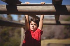 Ritratto del ragazzo che si esercita sulla barra di scimmia durante la corsa ad ostacoli fotografia stock libera da diritti