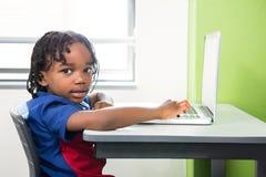 Ritratto del ragazzo che utilizza computer portatile nell'aula Fotografia Stock