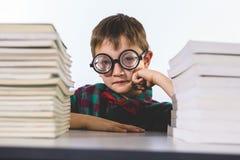 Ritratto del ragazzo con i libri sulla tavola in aula Immagini Stock