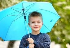 Ritratto del ragazzo con l'ombrello blu in pioggia immagine stock libera da diritti