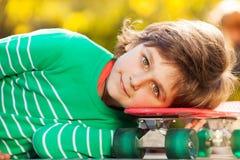 Ritratto del ragazzo con la sua testa sul pattino Fotografie Stock