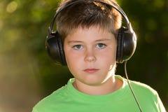Ritratto del ragazzo con le cuffie all'aperto Immagini Stock Libere da Diritti