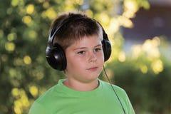 Ritratto del ragazzo con le cuffie all'aperto Immagine Stock