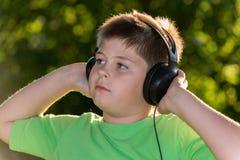 Ritratto del ragazzo con le cuffie all'aperto Immagini Stock