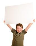 Ritratto del ragazzo del bambino in giovane età che tiene segno in bianco Immagine Stock