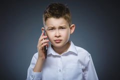 Ritratto del ragazzo di offesa con il cellulare o il telefono cellulare Emozione umana negativa immagine stock