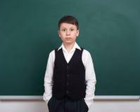 Ritratto del ragazzo di scuola vicino al fondo in bianco verde della lavagna, vestito in vestito classico, un allievo, concetto d Fotografia Stock Libera da Diritti