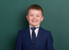 Ritratto del ragazzo di scuola vicino al fondo in bianco verde della lavagna, vestito in vestito nero classico, un allievo, conce Fotografie Stock