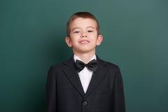 Ritratto del ragazzo di scuola vicino al fondo in bianco verde della lavagna, vestito in vestito nero classico, un allievo, conce Fotografie Stock Libere da Diritti