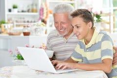 Ritratto del ragazzo e del nonno con un computer portatile Fotografia Stock Libera da Diritti