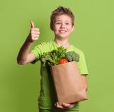 Ritratto del ragazzo felice che mostra i pollici sul gesto, isolato sopra il g immagine stock libera da diritti