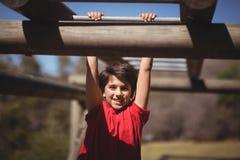 Ritratto del ragazzo felice che si esercita sulla barra di scimmia durante la corsa ad ostacoli fotografia stock libera da diritti
