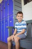 Ritratto del ragazzo sorridente che si siede sul banco dagli armadi Fotografia Stock