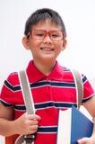 Ritratto del ragazzo sorridente con il sacchetto ed il libro. Immagini Stock