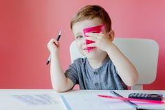 Ritratto del ragazzo sveglio del bambino a casa che fa compito Poco bambino concentrato che scrive con la matita variopinta, all' fotografie stock