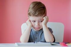 Ritratto del ragazzo sveglio del bambino a casa che fa compito Poco bambino concentrato che scrive con la matita variopinta, all' fotografia stock libera da diritti