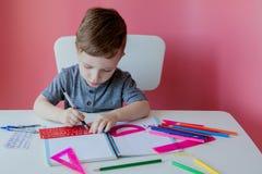 Ritratto del ragazzo sveglio del bambino a casa che fa compito Poco bambino concentrato che scrive con la matita variopinta, all' fotografia stock