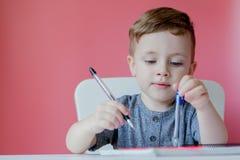 Ritratto del ragazzo sveglio del bambino a casa che fa compito Poco bambino concentrato che scrive con la matita variopinta, all' immagini stock