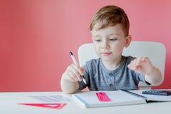Ritratto del ragazzo sveglio del bambino a casa che fa compito Poco bambino concentrato che scrive con la matita variopinta, all' immagine stock libera da diritti