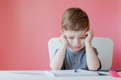 Ritratto del ragazzo sveglio del bambino a casa che fa compito Poco bambino concentrato che scrive con la matita variopinta, all' immagini stock libere da diritti