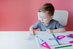 Ritratto del ragazzo sveglio del bambino a casa che fa compito Poco bambino concentrato che scrive con la matita variopinta, all' immagine stock
