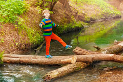Ritratto del ragazzo sveglio che attraversa il fiume di estate Fotografia Stock Libera da Diritti