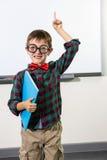 Ritratto del ragazzo sveglio con il taccuino che solleva mano in aula Fotografia Stock Libera da Diritti