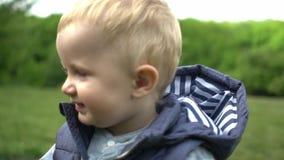 Ritratto del ragazzo sveglio di un anno che fa i suoi primi punti con sua madre nel movimento lento del parco archivi video