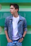 Ritratto del ragazzo teenager attraente bello che resta all'aperto vicino alla vecchia parete verde Fotografie Stock Libere da Diritti
